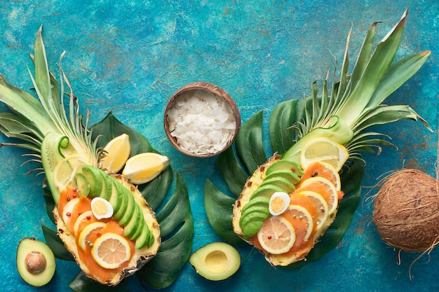 レモンとウズラの卵とスモークサーモンとアボカドのスライスとパイナップルボートのトップビュー Premium写真