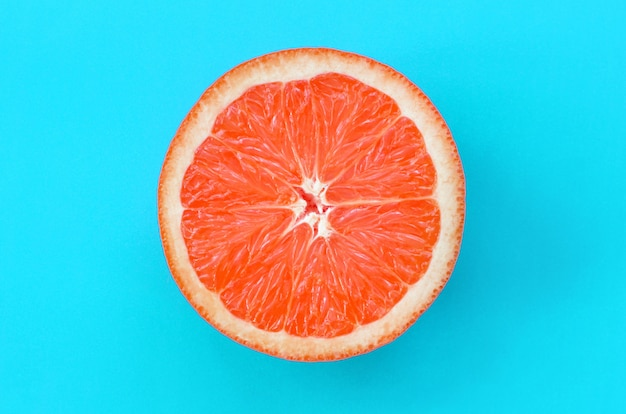 Top view of an one grapefruit slice on bright background in blue color. Premium Photo