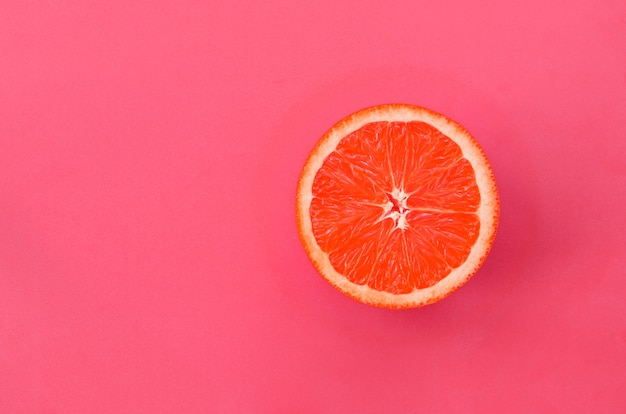 Top view of a one grapefruit slice on bright background in light pink color. Premium Photo