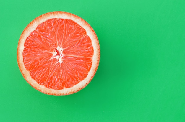 Top view of an one grapefruit slice on bright green Premium Photo