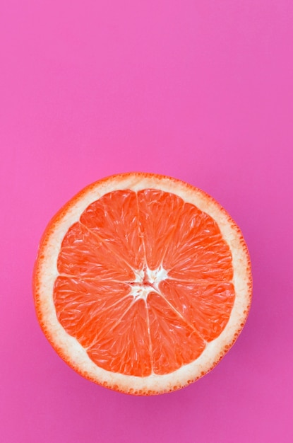 Top view of an one grapefruit slice on bright purple color Premium Photo
