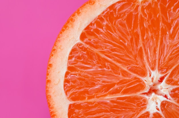Top view of an one grapefruit slice on bright purple Premium Photo