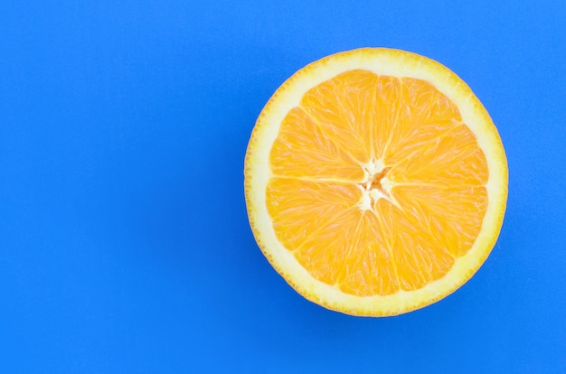 Top view of a one orange fruit slice on bright background in blue color Premium Photo