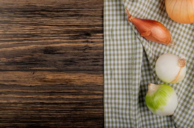 Top view of onions as shallot sweet and white ones on plaid cloth and wooden background with copy space Free Photo
