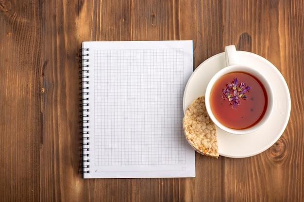 Quaderno blu aperto vista dall'alto con una tazza di tè sulla scrivania marrone Foto Gratuite