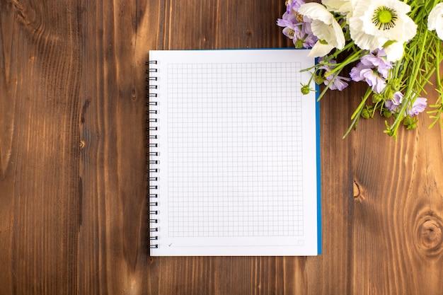Quaderno blu aperto vista dall'alto con fiori sulla scrivania marrone Foto Gratuite