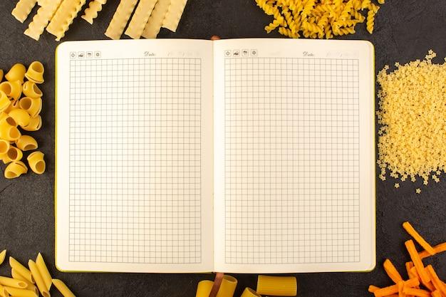 Un quaderno aperto vista dall'alto insieme a diversi formati di pasta cruda gialla isolato su sfondo scuro pasto cibo italia pasta Foto Gratuite