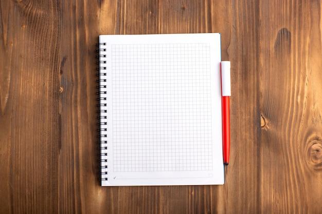 Quaderno aperto vista dall'alto con la penna sulla scrivania marrone Foto Gratuite