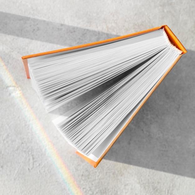 Vista dall'alto del libro con copertina rigida aperto sul tavolo Foto Gratuite