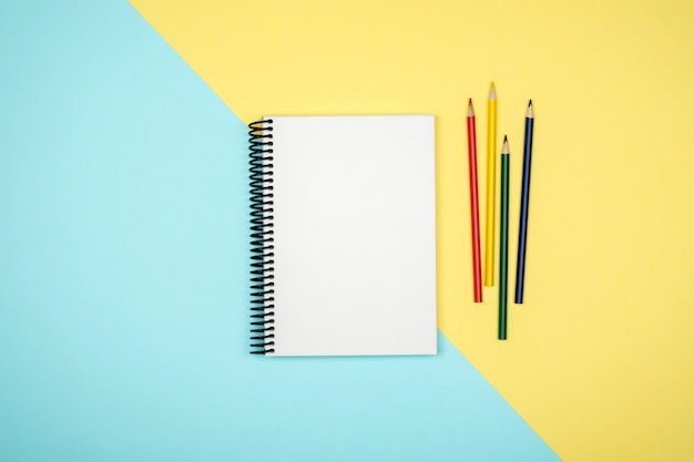 Top view of open spiral blank notebook on colorful desk Premium Photo