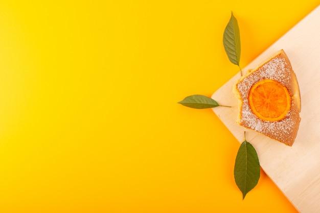 Una vista dall'alto fetta d'arancia torta dolce delizioso gustoso sulla scrivania in legno color crema e sfondo giallo biscotto di zucchero dolce Foto Gratuite