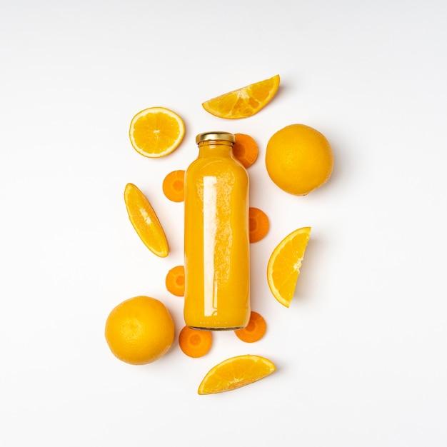 Vista dall'alto di succo d'arancia in bottiglia Foto Gratuite