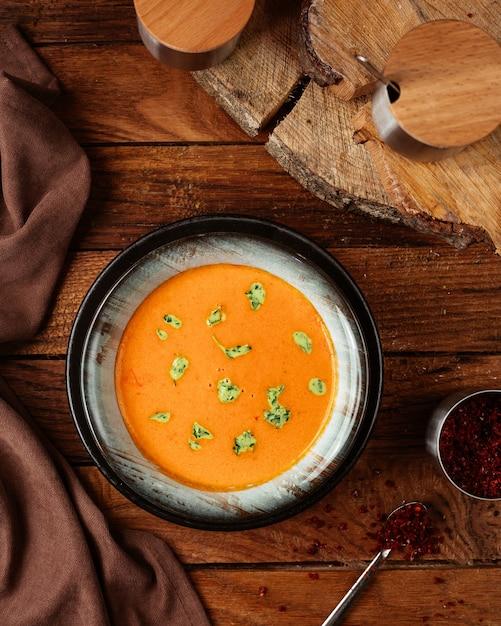 Una zuppa di arancia vista dall'alto con foglie sul pasto di cibo scrivania in legno Foto Gratuite