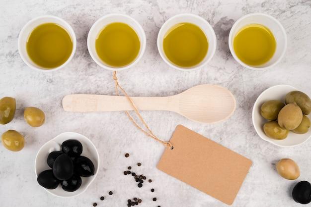 Vista dall'alto olio d'oliva e cucchiaio biologici Foto Gratuite