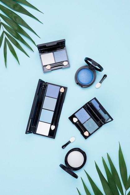 Pacchetto di vista superiore di prodotti di bellezza su sfondo blu Foto Gratuite