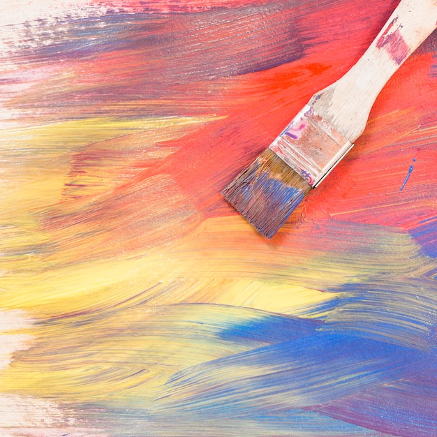 Top view of paint brush on bright colorful brush stroke textured Free Photo