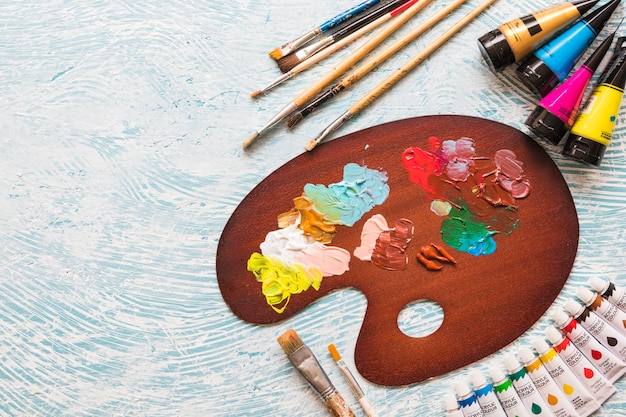 Top view paint palette surrounded by painting material Free Photo
