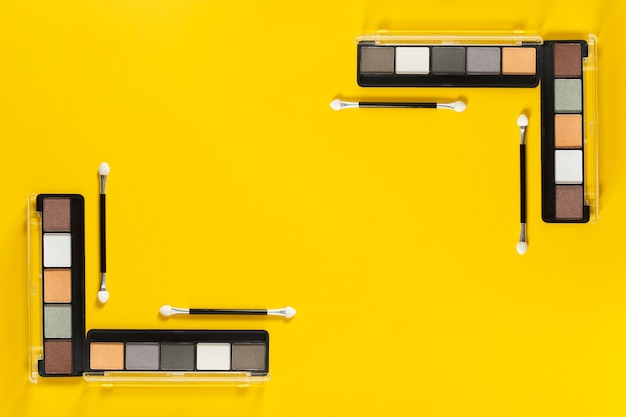 Top view of palettes on yellow background with copy space Free Photo