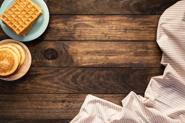 Top view pancakes and waffles with striped sheet Free Photo