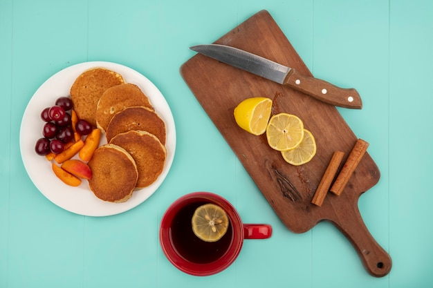 Top view of pancakes with cherries and apricot slices in plate and cup of coffee with lemon slices and cinnamon with knife on cutting board on blue background Free Photo