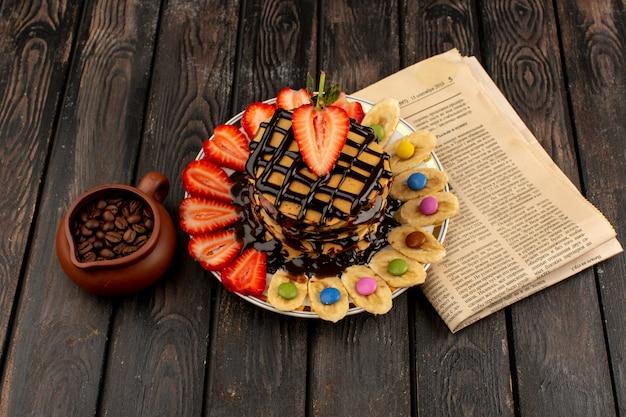 茶色の机の上の果物と平面図パンケーキ 無料写真