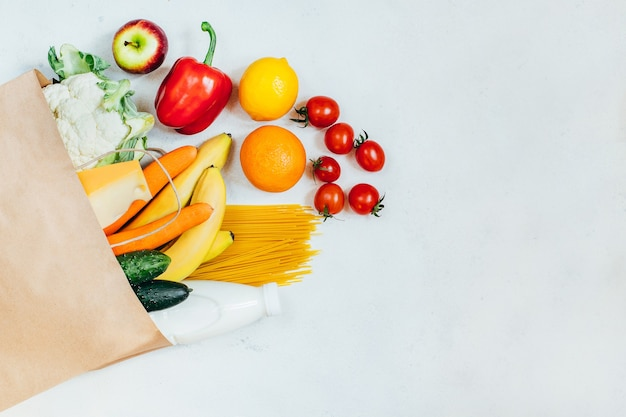 Top view of paper bag with fruits, vegetables, spaghetti, cheese, milk on white background Premium Photo
