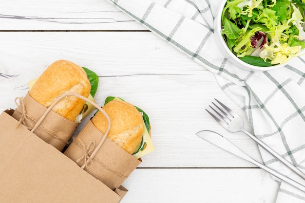 Top view of paper bag with two sandwiches inside and salad Free Photo