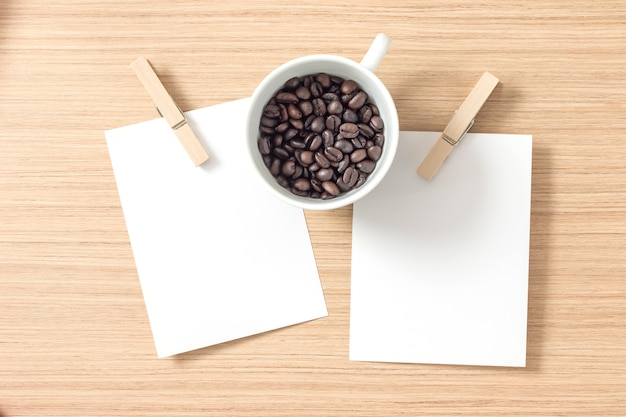 Top view of paper or cardboard with clothes pegs and coffee bean Premium Photo