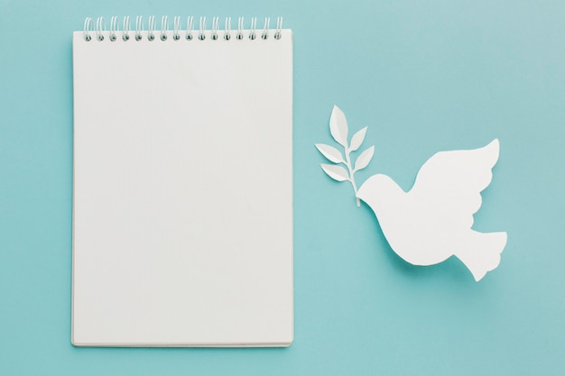 Top view of paper dove with notebook Free Photo