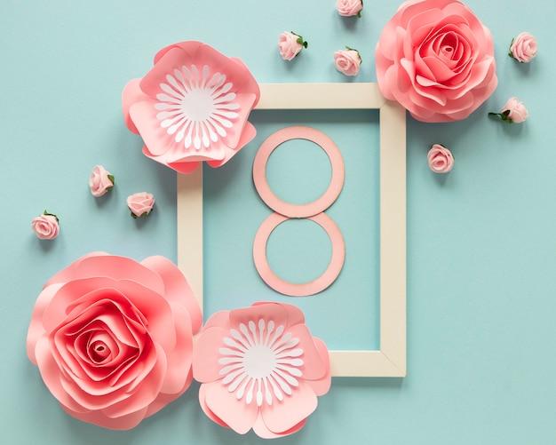 Vista dall'alto di fiori di carta con cornice e data per la festa della donna Foto Gratuite