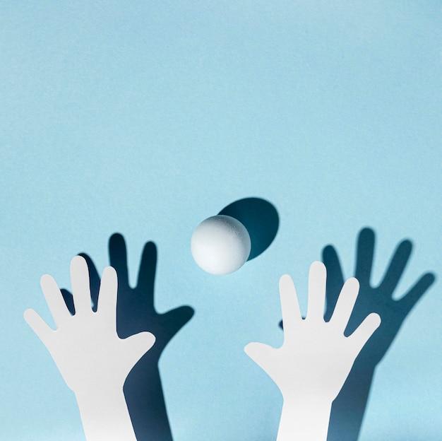 Vista dall'alto delle mani di carta con pallina da ping pong Foto Gratuite