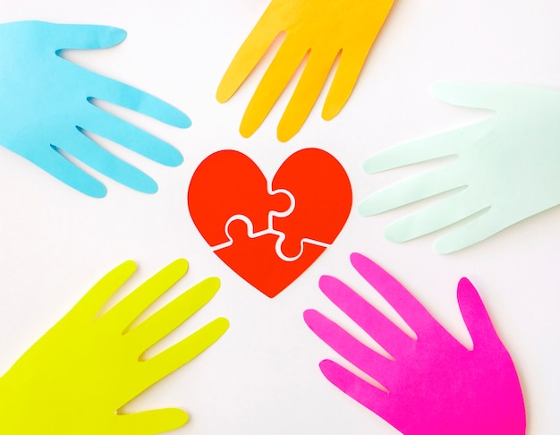Top view of paper hands with puzzle paper heart Free Photo