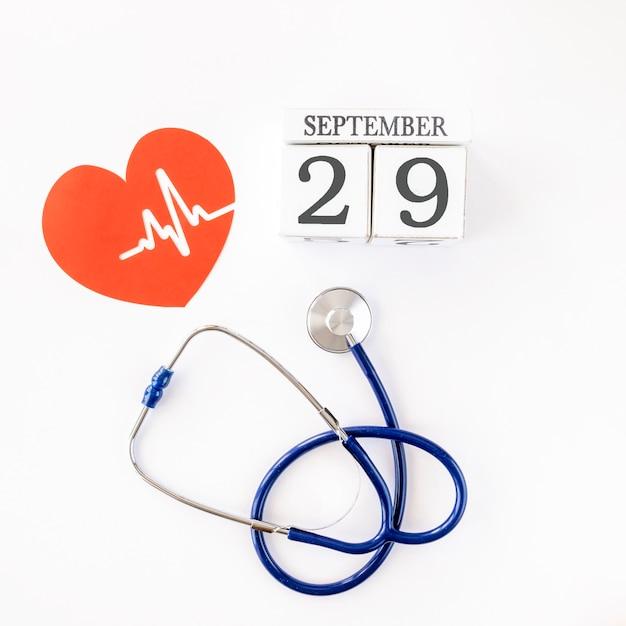 Vista dall'alto del cuore di carta con data e stetoscopio Foto Gratuite