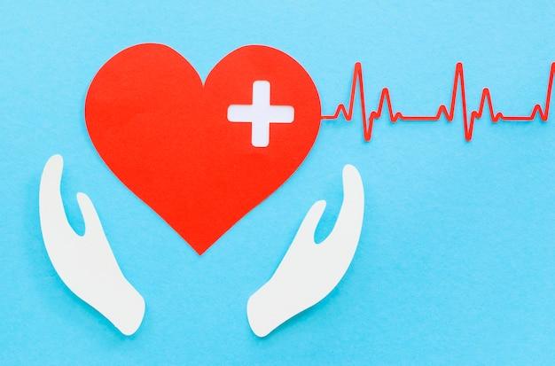 Vista dall'alto del cuore di carta con battito cardiaco e mani Foto Gratuite