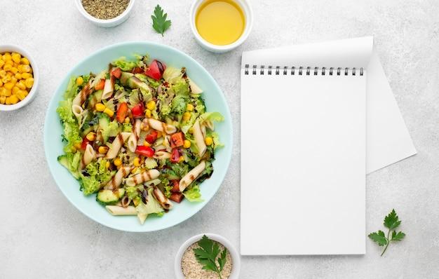 Vista dall'alto di insalata di pasta con aceto balsamico e taccuino in bianco Foto Gratuite