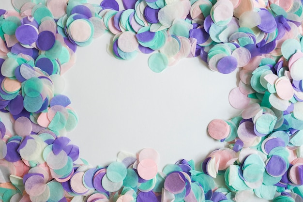 Top view pastel color confetti with space in the middle Free Photo