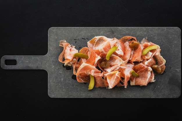 Top view of pata negra spanish ham with pickled cucumbers served on the board Free Photo