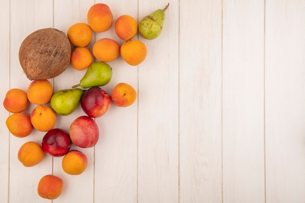 Top view of pattern of fruits as peach apricot pear coconut on wooden background with copy space Free Photo