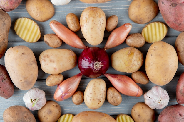 Top view of pattern of vegetables as sliced and whole potato shallot garlic and onion on wooden background Free Photo