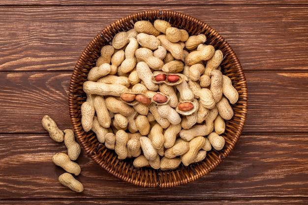 Вид сверху арахис в скорлупе в корзине на деревянном столе Бесплатные Фотографии