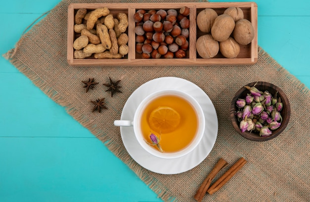 Вид сверху арахис с фундуком и грецкими орехами и чашка чая с корицей на голубом фоне Бесплатные Фотографии