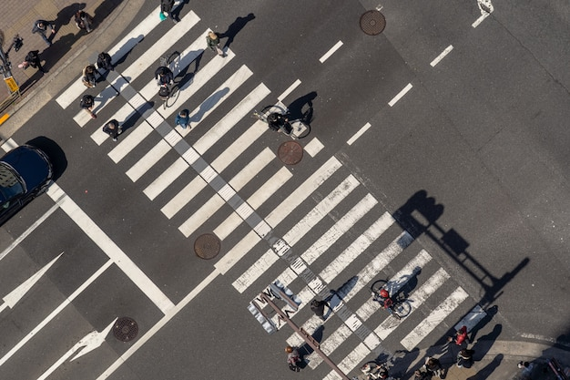Top view of pedestrians crowd undefined people walking overpass the street intersection cross-walk Premium Photo