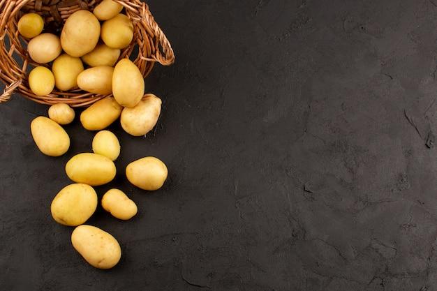 Вид сверху очищенная картошка целиком внутри корзины на темном полу Бесплатные Фотографии