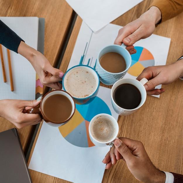 Vista dall'alto di persone in festa con tazze da caffè durante la riunione in ufficio Foto Gratuite
