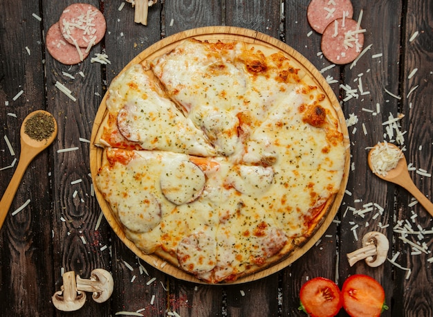 Top view of pepperoni pizza with sausage, tomato sauce, cheese and herb sprinkles Free Photo