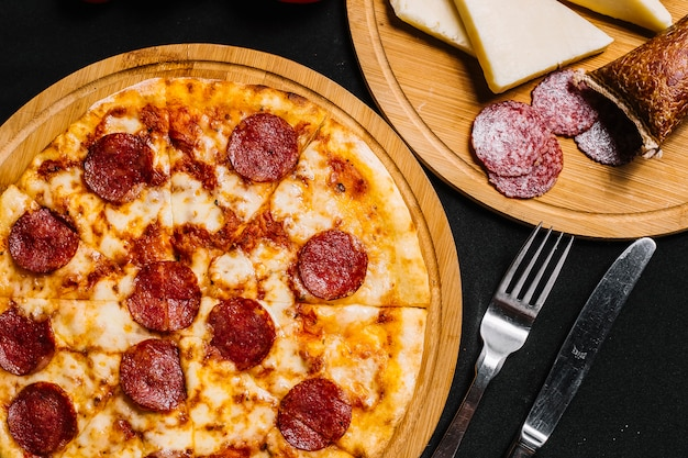 Top view of pepperoni pizza with tomato sauce and cheese Free Photo