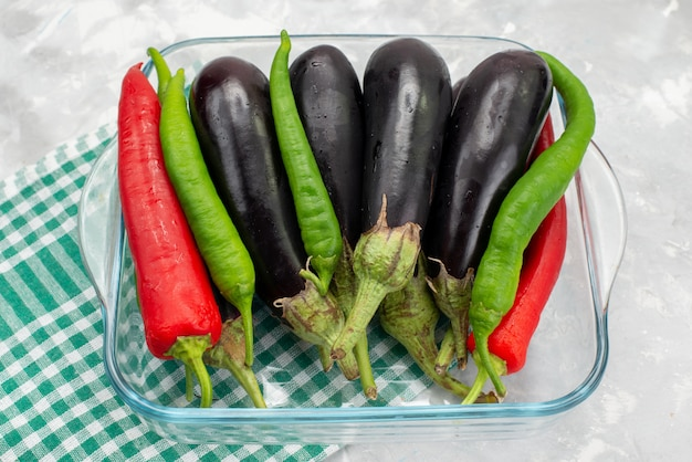 Peperoni e melanzane di vista dall'alto all'interno della ciotola di vetro trasparente sulla verdura cruda del pasto dell'alimento della scrivania luminosa Foto Gratuite