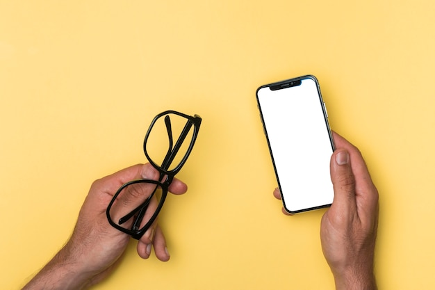 Top view person holding mockup smartphone Free Photo