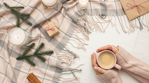 Top view of person holding mug with candles and blanket Free Photo