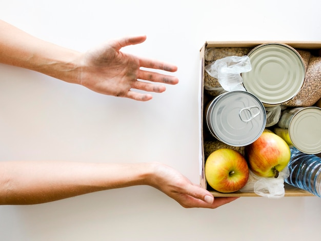 Top view of person receiving food donation box Premium Photo